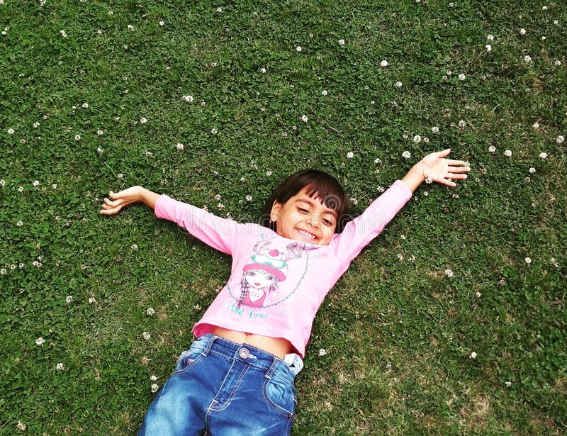 Girl Laying On Green Grass royalty free stock photography
