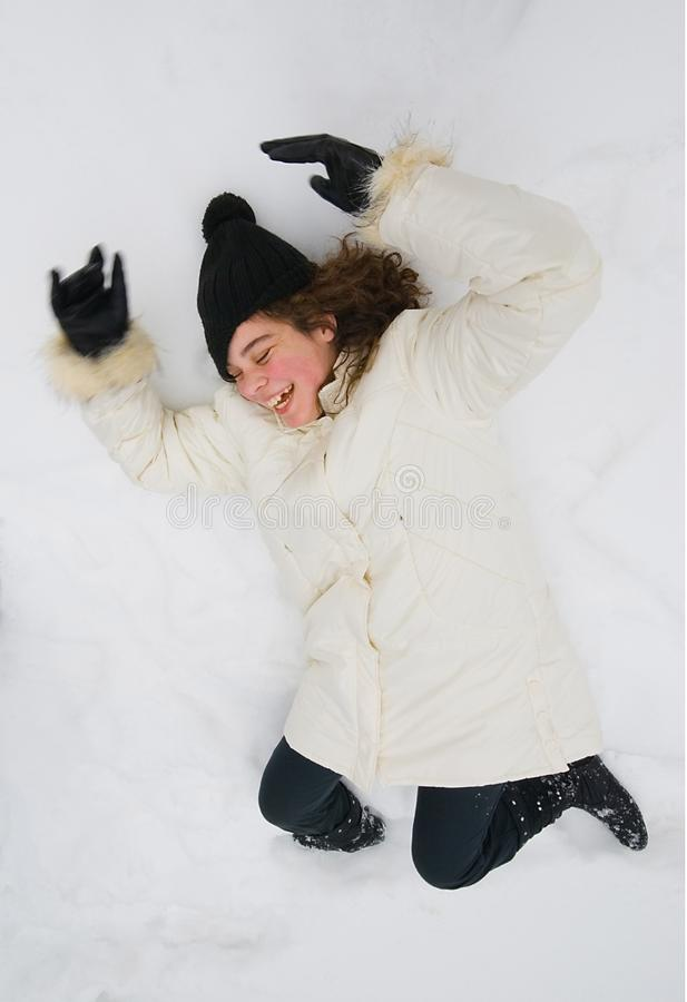Girl laying at snow royalty free stock photo