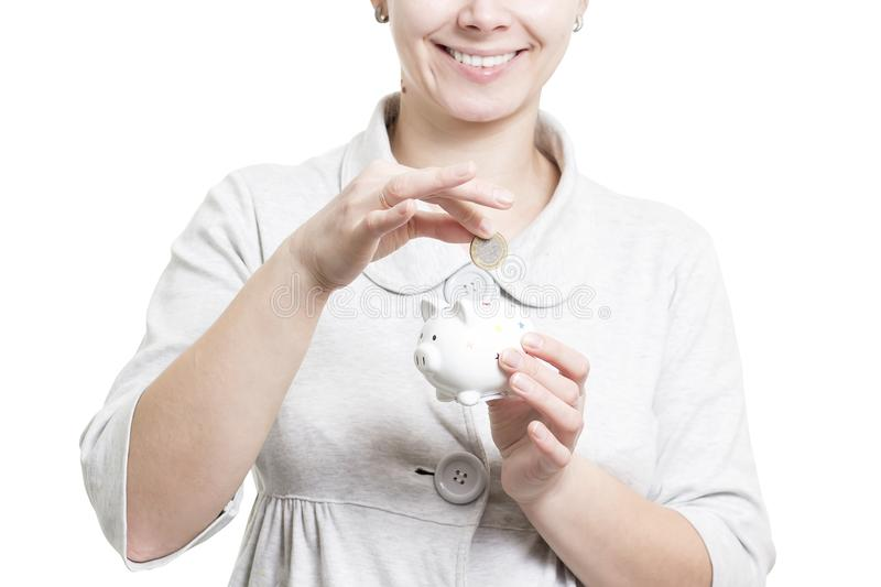 Girl lays coin in piggy bank. Collect and keep money at home. Piggy bank and coins concept. Woman with piggy bank and coin. Close-up isolated on white royalty free stock photos