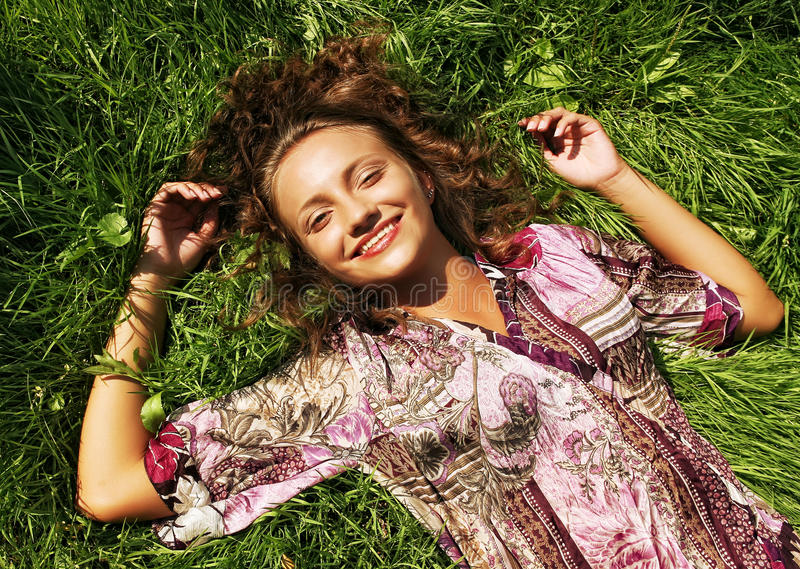 The girl lays on a grass a meadow. Summer day stock photo