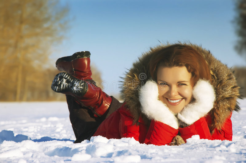 Girl lays on snow. Having clasped a head by hands royalty free stock photos