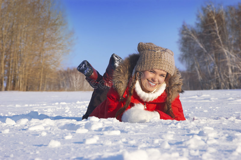 Girl lays on snow and smiles. Girl lays on snow having clasped a head by hands stock image