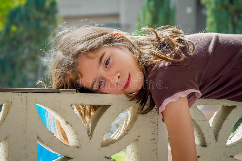 Girl On A Lazy Day. A young, tween girl, lays across a wall on a lazy day. She is relaxing and soaking in the sun stock photo