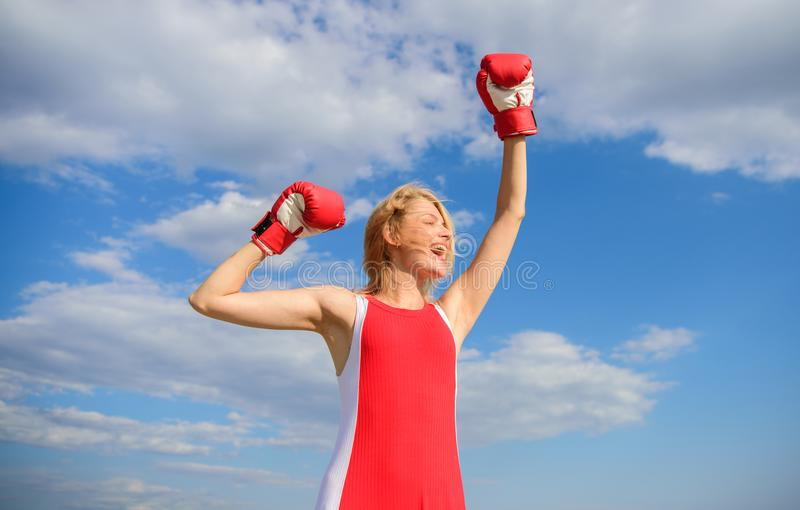 Girl leader promoting feminism. Woman boxing gloves raise hands blue sky background. Girl boxing gloves symbol struggle. For female rights and liberties stock photo