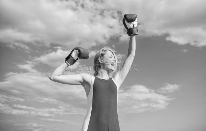 Girl leader promoting feminism. Woman boxing gloves raise hands blue sky background. Girl boxing gloves symbol struggle. For female rights and liberties royalty free stock image