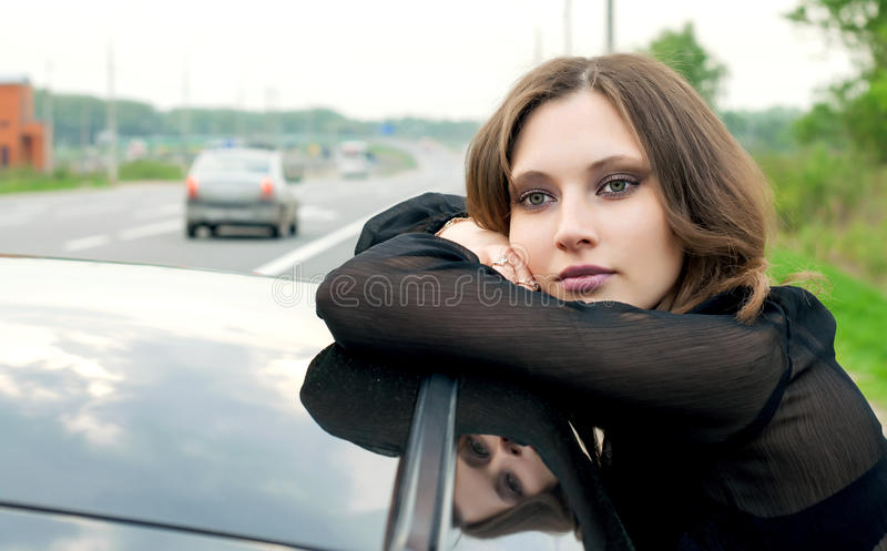 Girl leaning against a car outdoors stock images