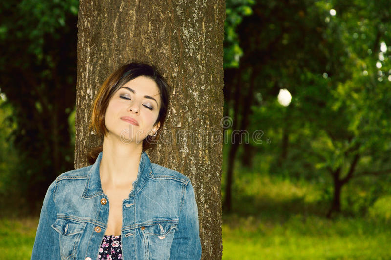 Girl leaning against a tree stock images