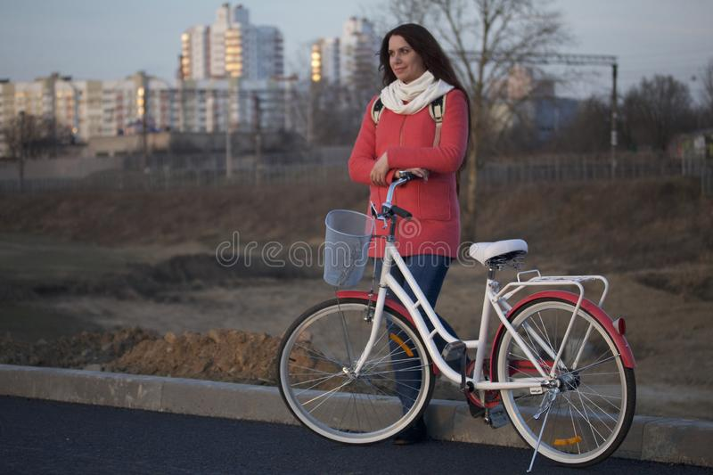 The girl leans on a parked bike. Rest on the spring cycle stock photos