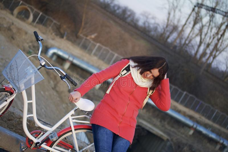 The girl leans on a parked bike and straightens her hair. Rest on the spring cycle royalty free stock image