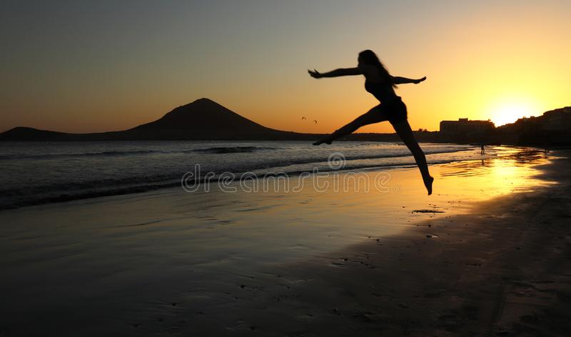 Girl leaps on a beach at sunset in Tenerife, Spain royalty free stock photography