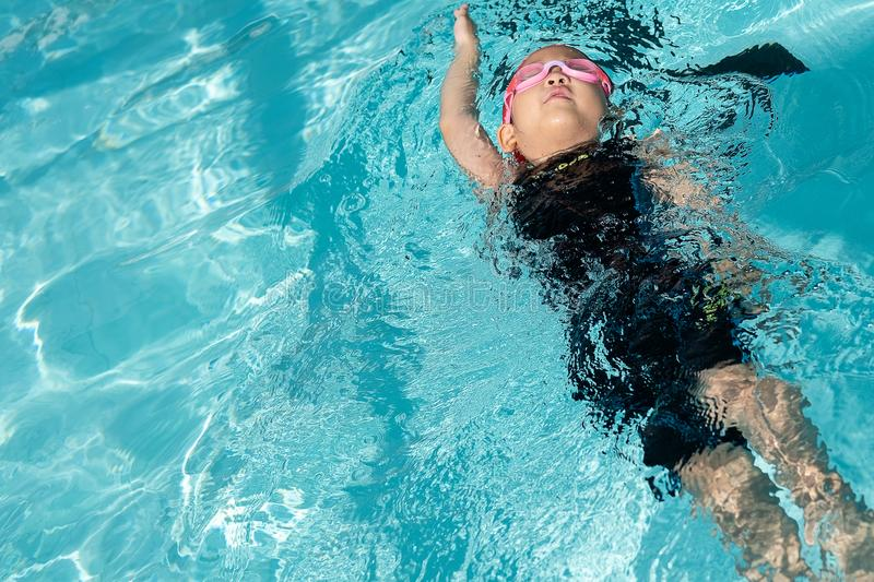 A girl learn how to swim in swimming class stock photo