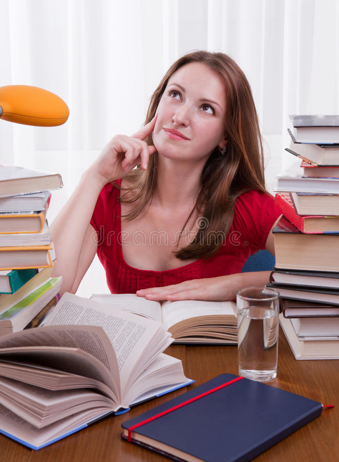 Girl learning at the desk. Girl studying at home with lot of books around royalty free stock photography
