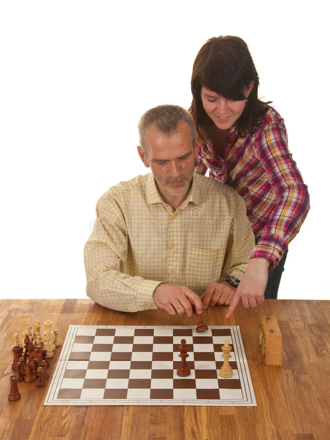 A girl is learning her father how to checkmate. A girl is teaching her father how to checkmate the enemy king stock photo