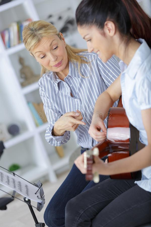 Girl learning how to play guitar with teacher stock images
