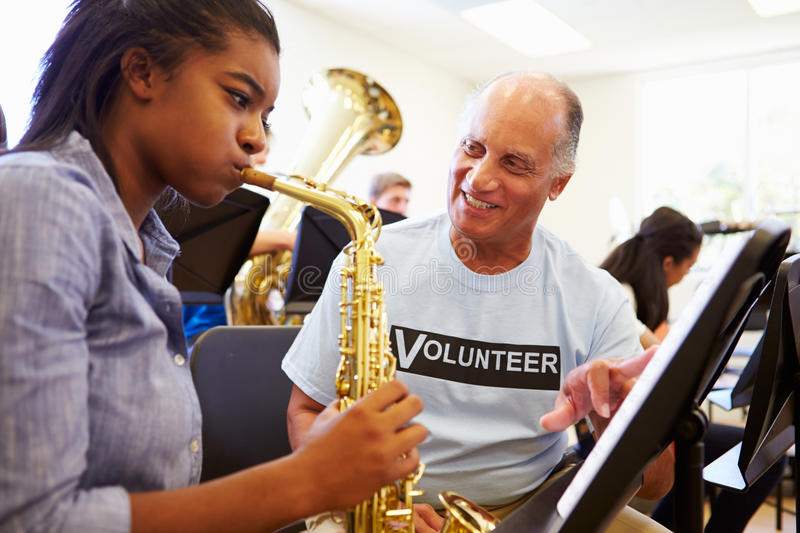 Girl Learning To Play Saxophone In High School Orchestra. With Help From Volunteer stock photos