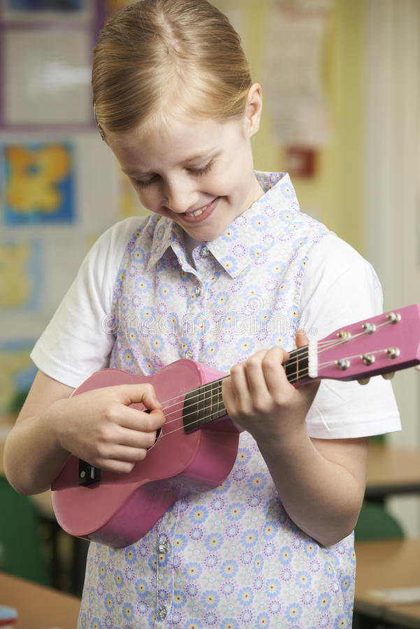 Girl Learning To Play Ukulele In School Music Lesson. Girl Learning To Play Ukulele In School Music Class royalty free stock photography