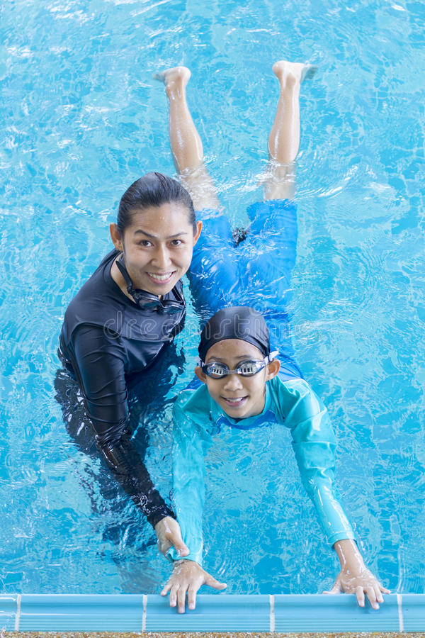Girl learning to swim with coach stock image