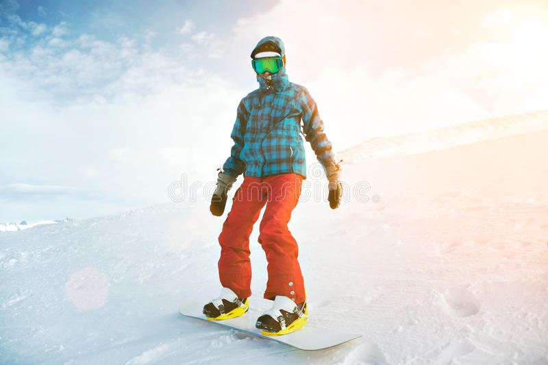 Girl learns snowboarding in mountains at winter stock photography