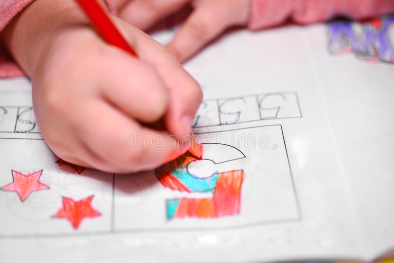 A girl learns to count, a girl colors a number five with a pencil. stock photography