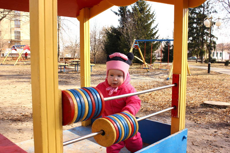 Girl learns to count on the playground. Smart girl learns to count on the playground stock photo