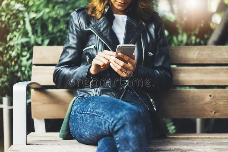 Girl in leather jacket holding smart phone on bench background sun atmospheric city, hipster using in female hands and texting stock photo