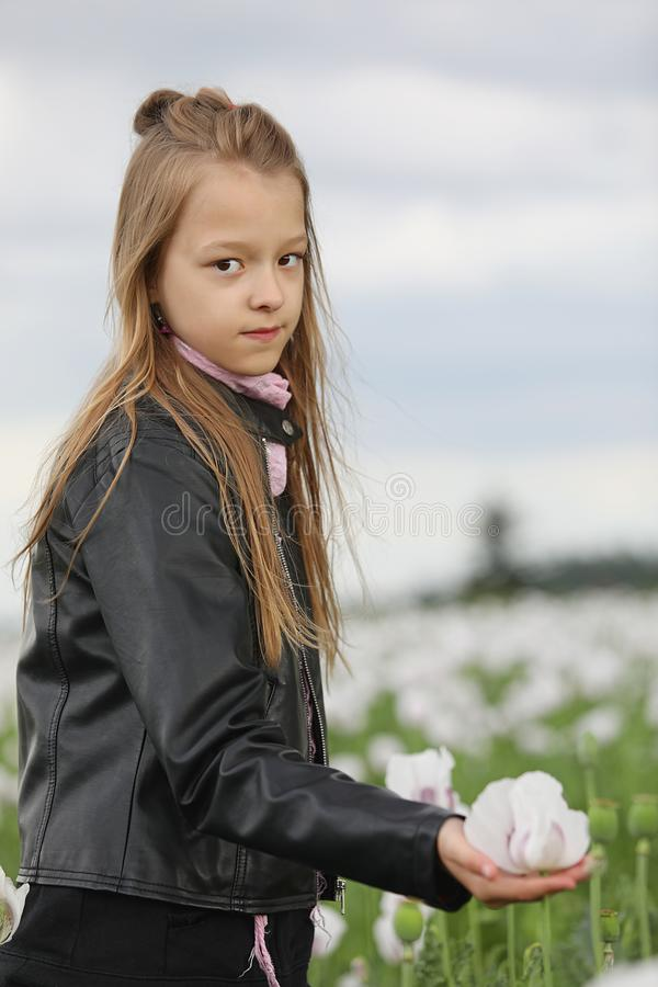 Girl in leather jacket holds in her palm white poppie. Young royalty free stock photography