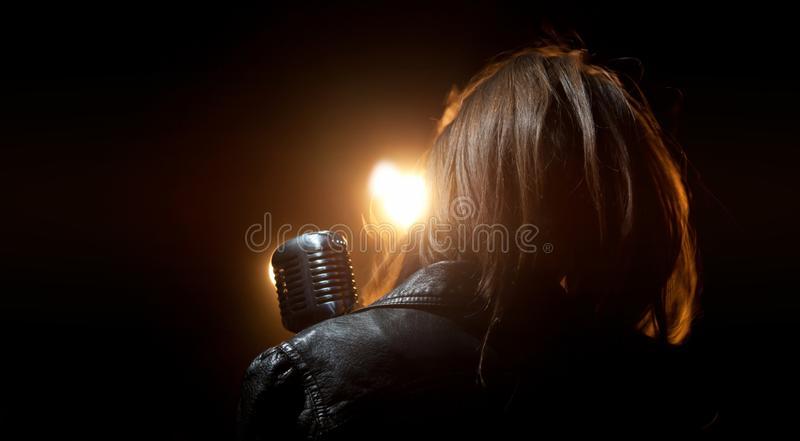 A girl in a leather jacket with a microphone in the light stock photo