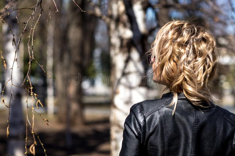 A girl in a leather jacket stands with her back royalty free stock photography