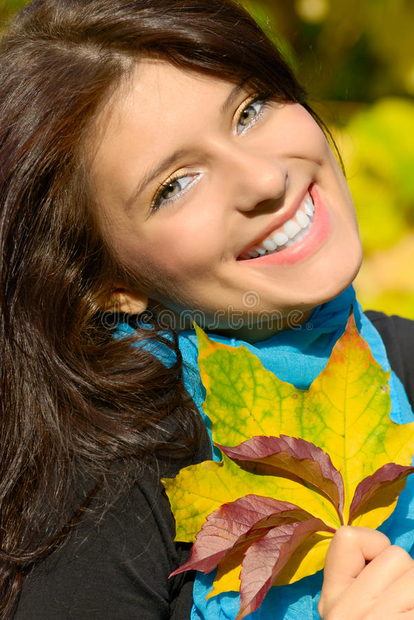 Girl with leaves. Portrait of a happy girl with golden autumn leaves in hand stock photos