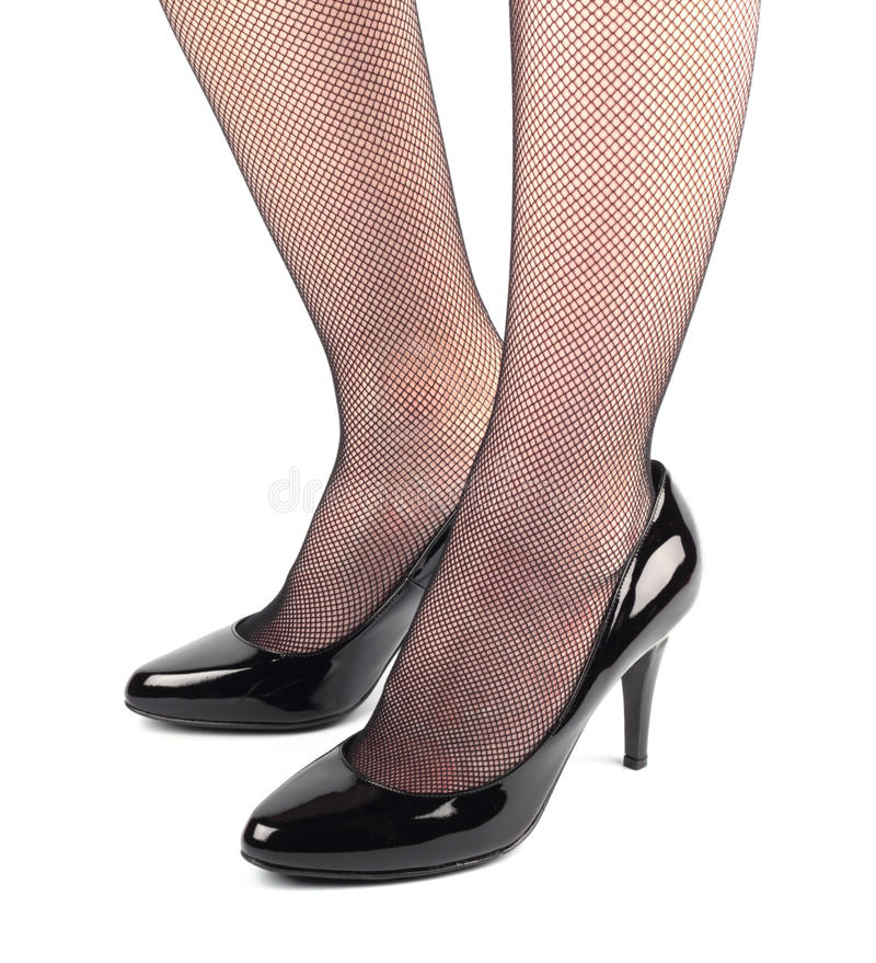 Girl legs in black patent leather shoes stock image