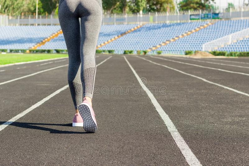 Girl legs in pink sport shoes standing on a running track with stadium stands. Sports and healthy concept.  stock image
