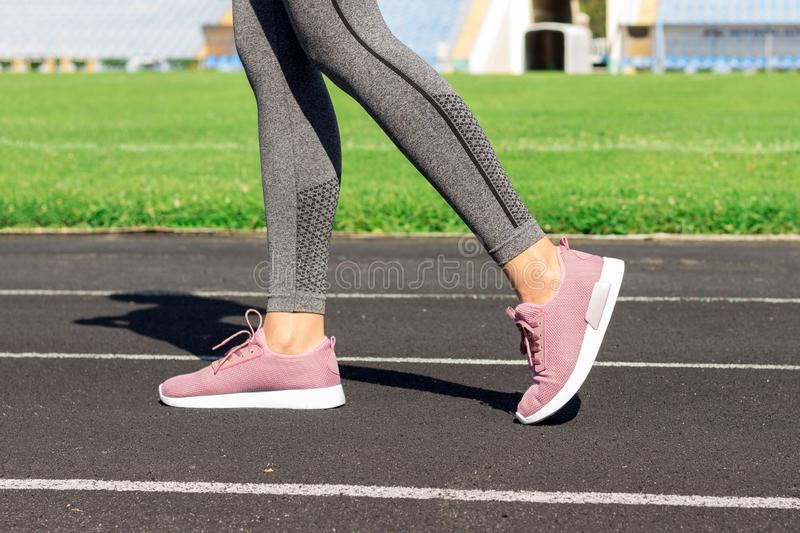 Girl legs in pink sport shoes standing on a running track with stadium stands. Sports and healthy concept.  royalty free stock photos
