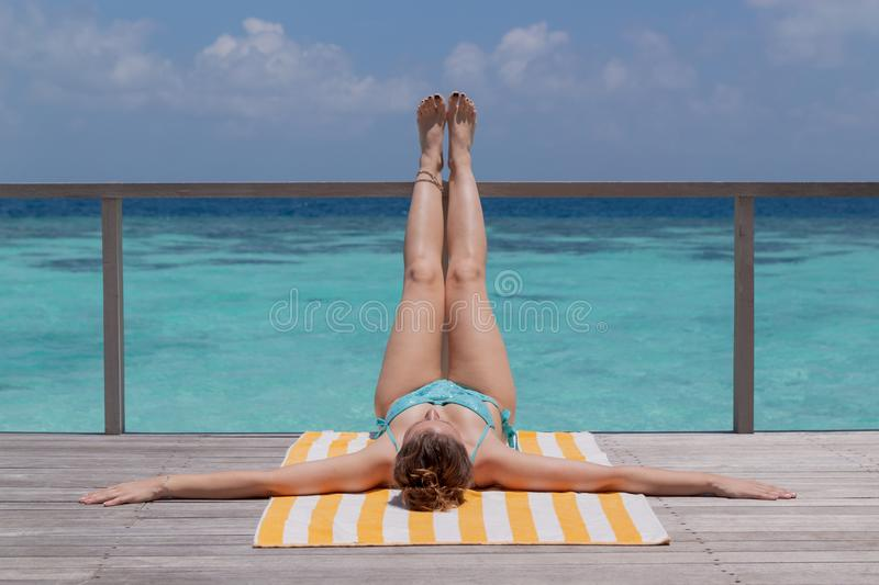 Young woman taking a tan on a terrace. Clear blue water as background stock image