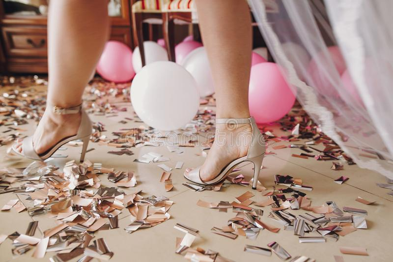 Girl legs in stylish white shoes walking on gold and silver confetti,bridal boudoir morning details before wedding ceremony. Hen. Shower. Christmas and new year royalty free stock photo