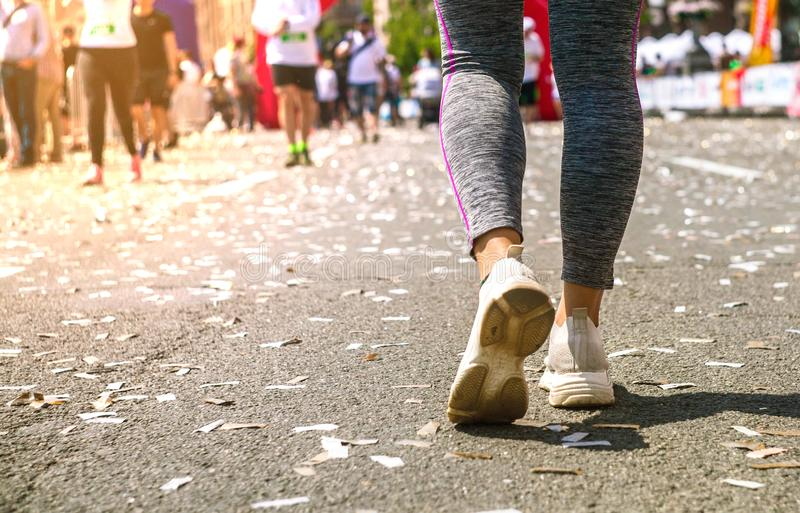 Girl legs in white sport shoes standing on a running track with stadium stands. Sports and healthy concept stock photos