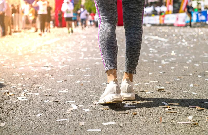 Girl legs in white sport shoes standing on a running track with stadium stands. Sports and healthy concept royalty free stock images