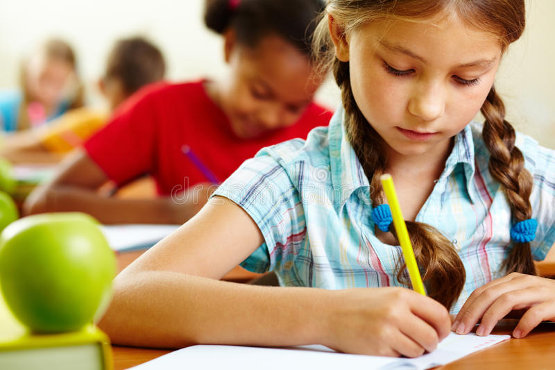 Girl at lesson. Portrait of lovely girl drawing in copybook at lesson royalty free stock photo