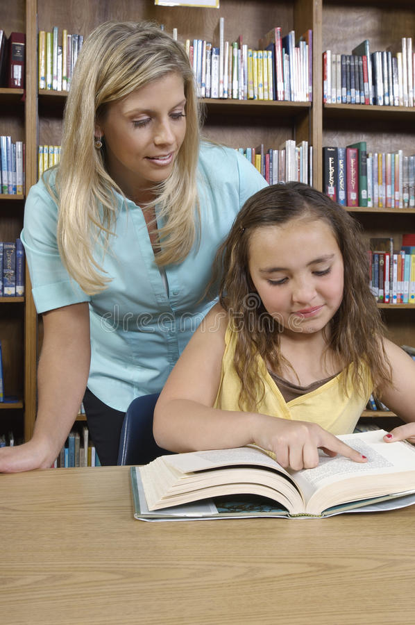 Girl And Librarian Reading Book stock image
