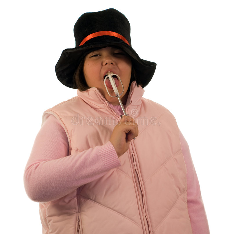 Girl Licking Beater. A young girl wearing winter clothes, licking a beater with whipped cream on it, isolated against a white background stock images