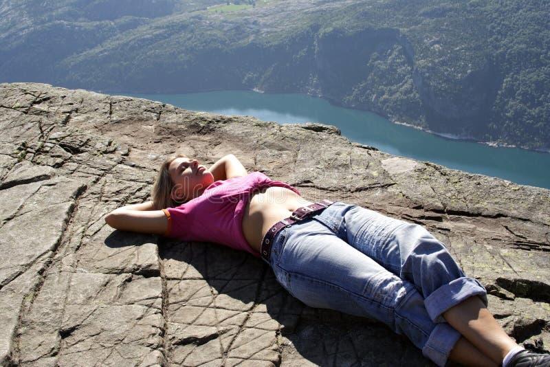 Girl lie on fjord cliff edge. In Norwegian fjord - nord europe stock image