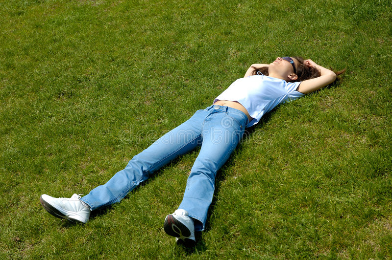 Girl lie in grass summer nature relaxed. Young woman relaxing lying in green grass having fun simmer nature royalty free stock photo