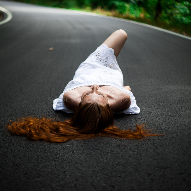 Girl lie on a road - hitchhiking stock photos