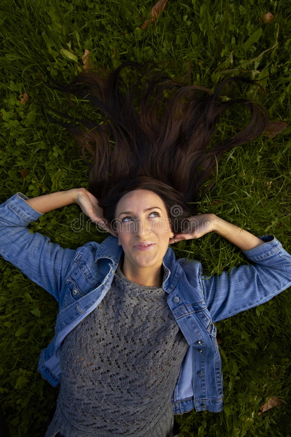 Girl lies on the emerald grass. Girl lies hands behind his head and swept her long black hair on the emerald grass among fallen red oak leaves smiling broadly stock photo
