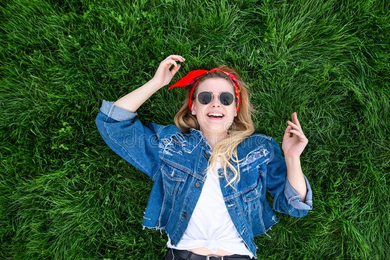 Girl lies on a green lawn, looks at the camera and rejoices. Portrait of a happy, stylish young woman lying on the grass stock photos