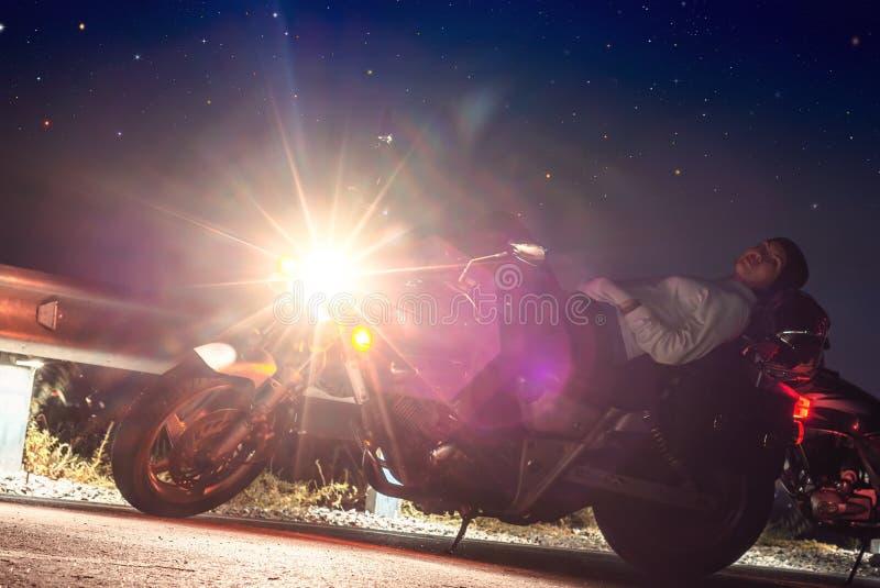 The girl lies on the motorcycle seat at night. Luminous headlight stock image