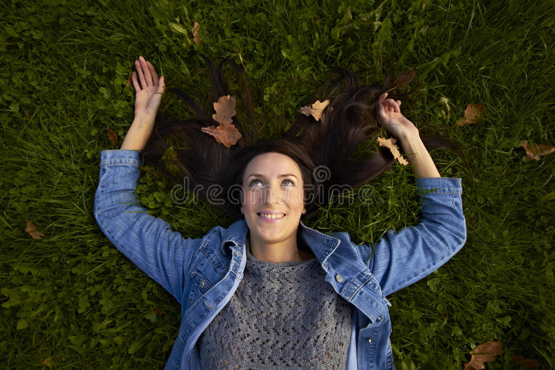 Girl lies outstretched arms on the emerald grass. Girl lies outstretched arms and swept her long black hair on the emerald grass among fallen red oak leaves stock images