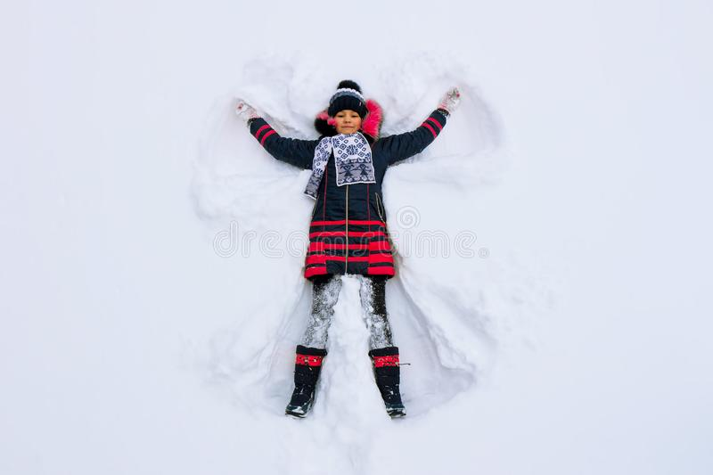 The girl lies in the snow and makes a snow angel royalty free stock photo