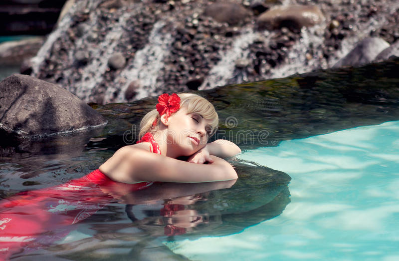 The girl lies in water. The girl in a red dress lies in water stock photos
