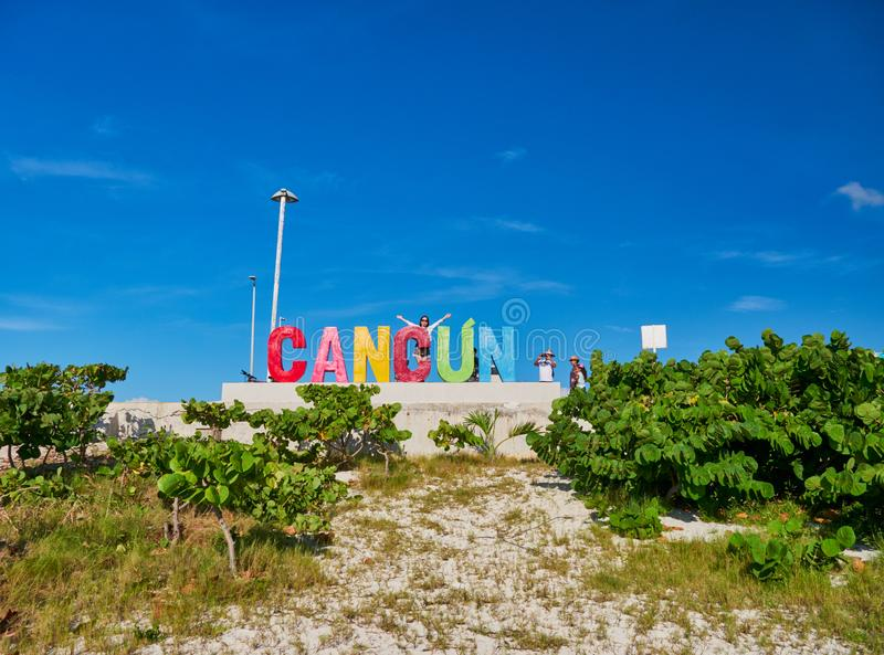 Girl lifts her arms in Cancun sign stock images