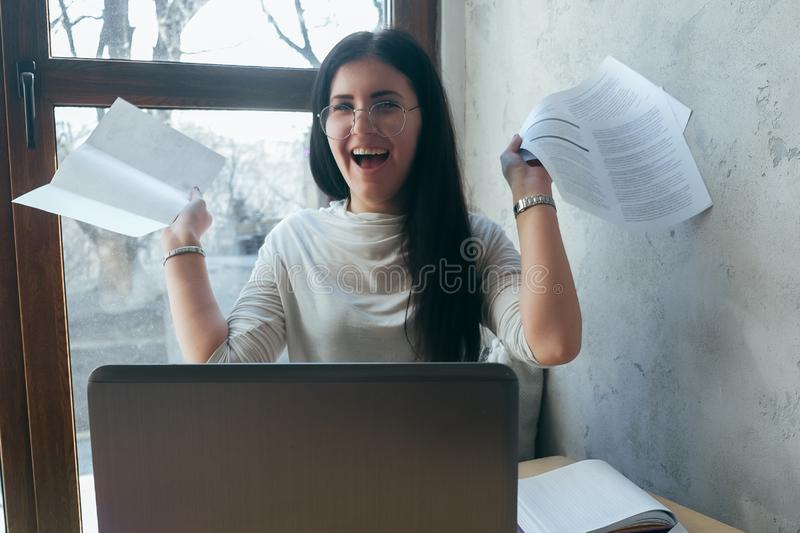 The girl in light clothes holds her arms outstretched documents and smiles. Coworking at home, work in a cafe. On the desktop is royalty free stock photo